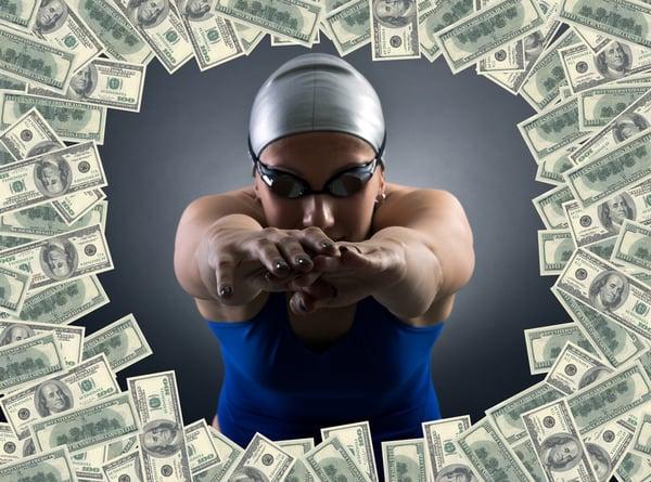 Female-swimmer-diving-through-circle-of-money