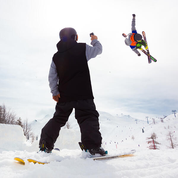 Man-recording-ski-jump-of-friend