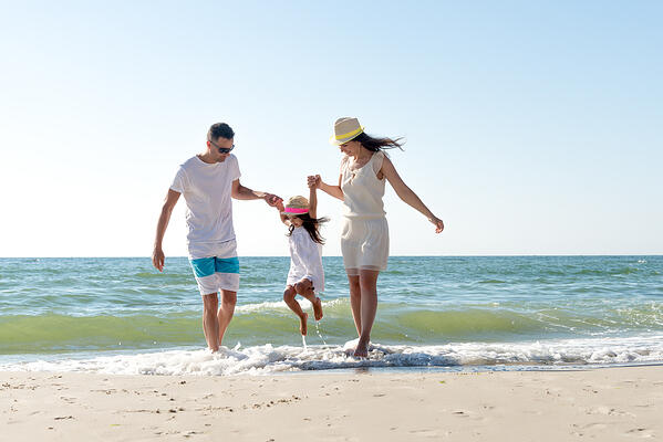 Couple-and-child-playing-on-the-beach-shore