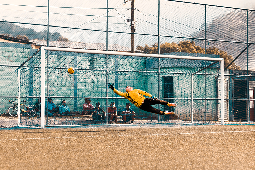 An action shot of a goalie making a save.
