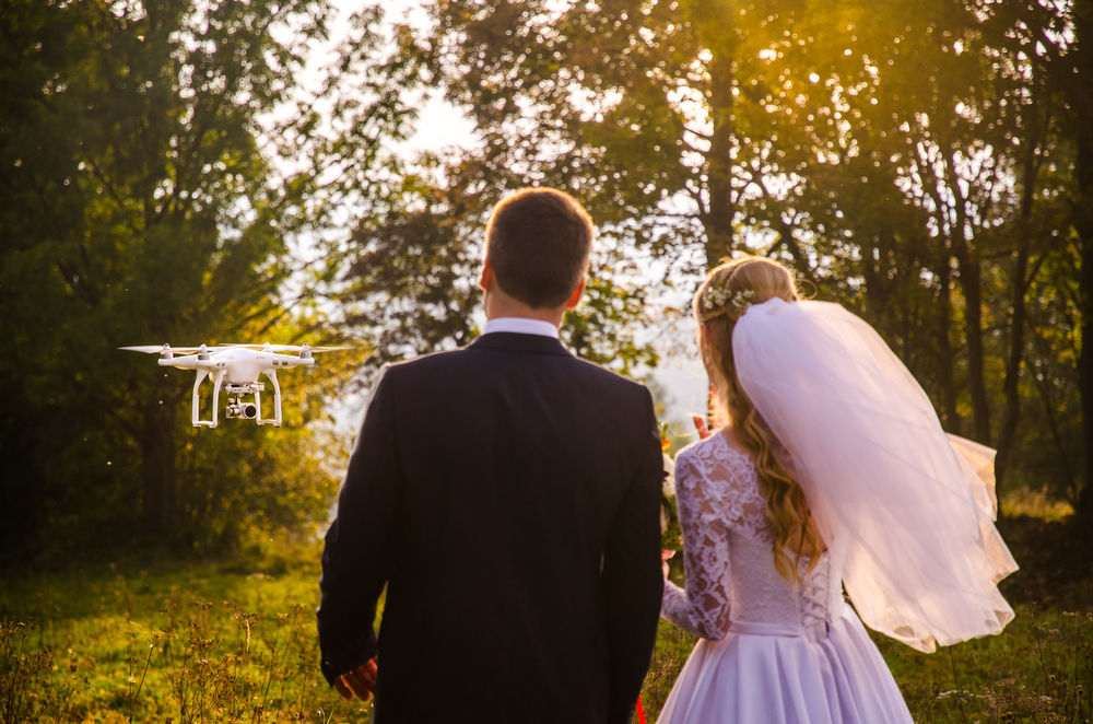 Bride-and-groom-look-at-drone-taking-video