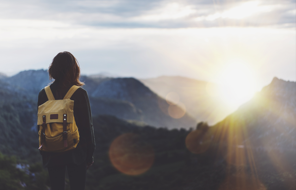 Woman-stands-in-nature-watching-the-sun-rise