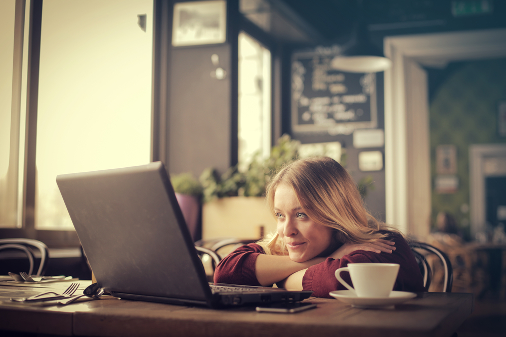 Young-woman-watching-a-video-on-her-computer-at-a-coffee-shop