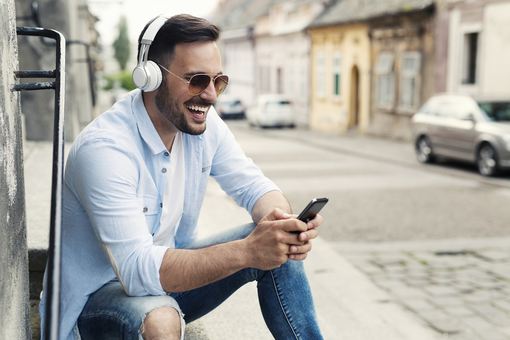 Young-man-watching-a-video-on-his-phone-in-an-urban-setting