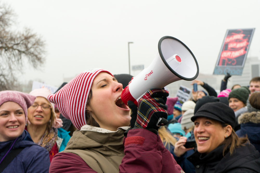 Woman-speaking-into-a-microphone-at-a-protest-march