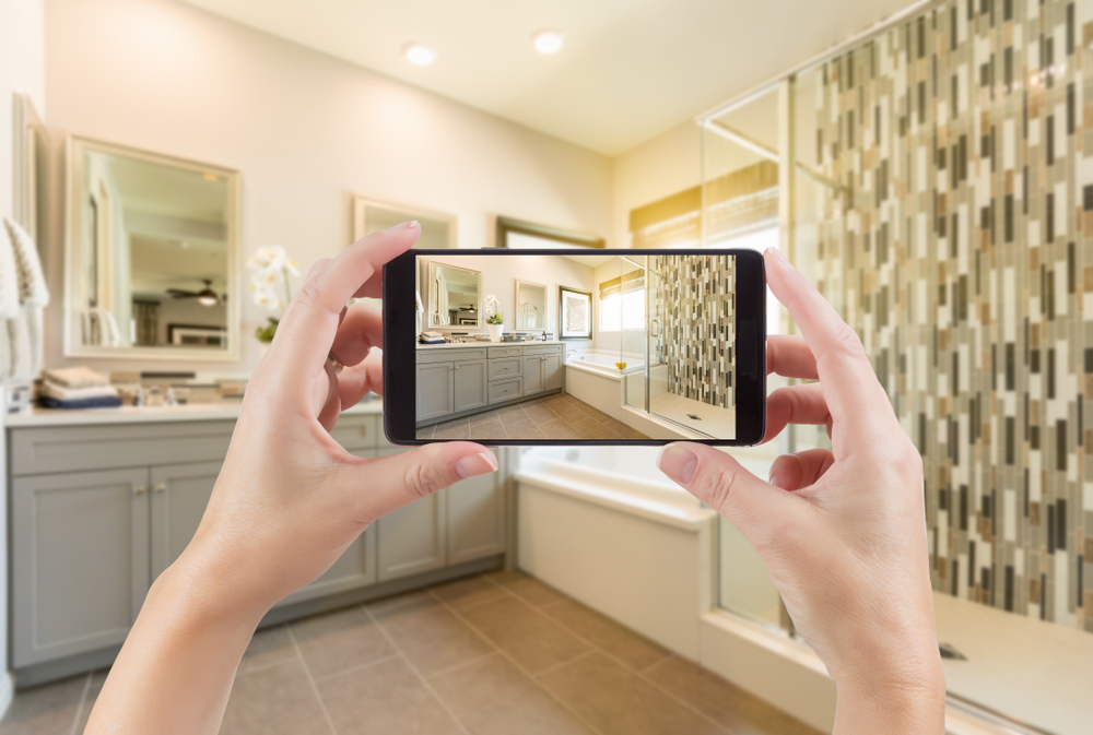 Woman-holds-up-a-camera-phone-to-record-a-remodeled-bathroom