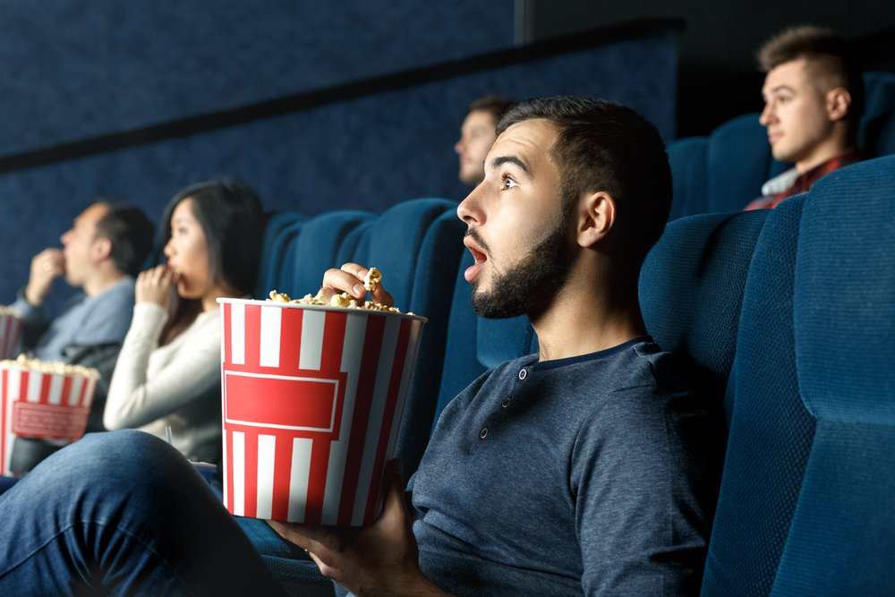 Young-man-surprised-at-movie-theater-while-eating-popcorn