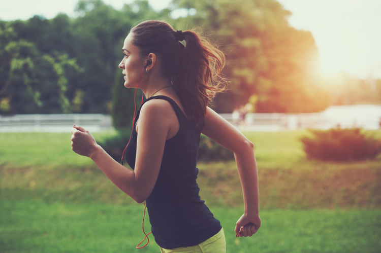 Young-woman-running-while-listening-to-music-through-earbuds