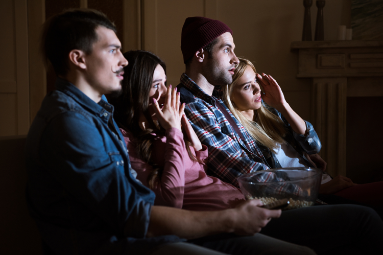 Two-young-couples-watch-scary-movie-at-home