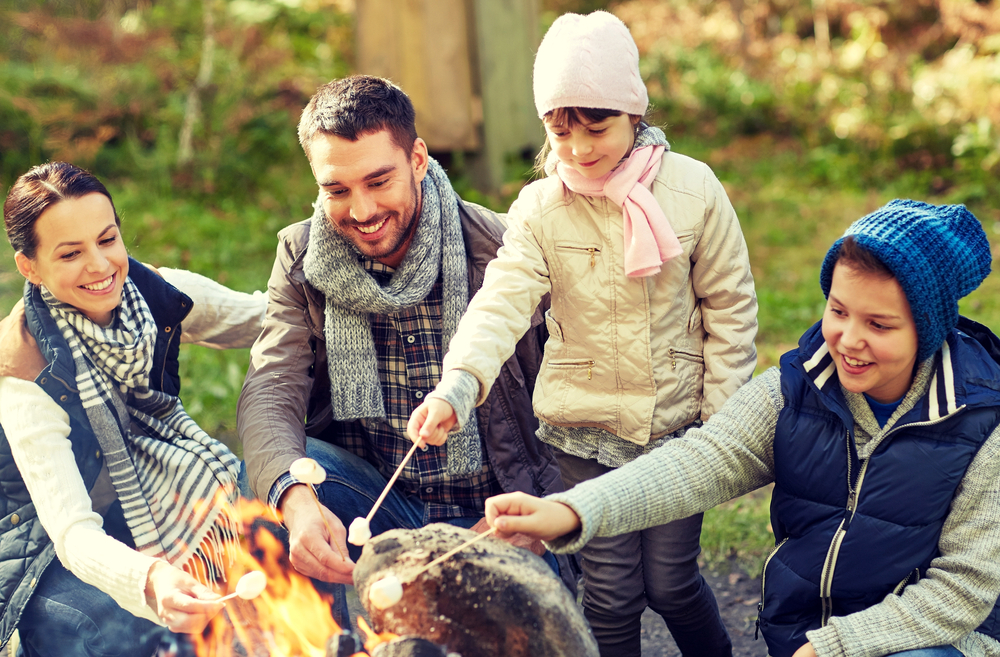 Happy-family-of-four-roasting-marshmallows-over-an-outdoor-fire