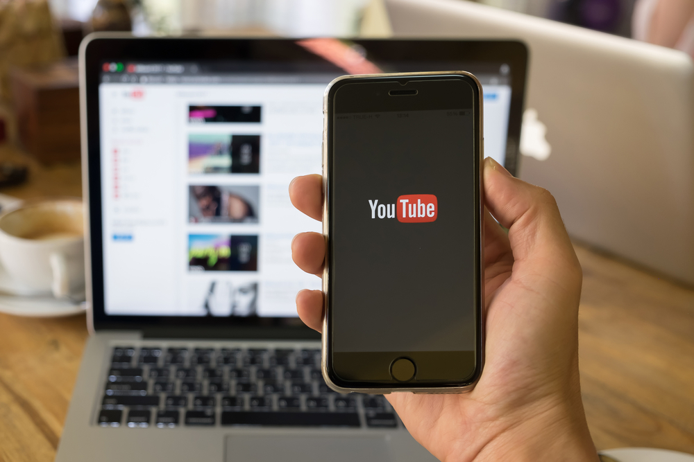 Phone-featuring-YouTube-logo-in-front-of-laptop-with-YouTube-website