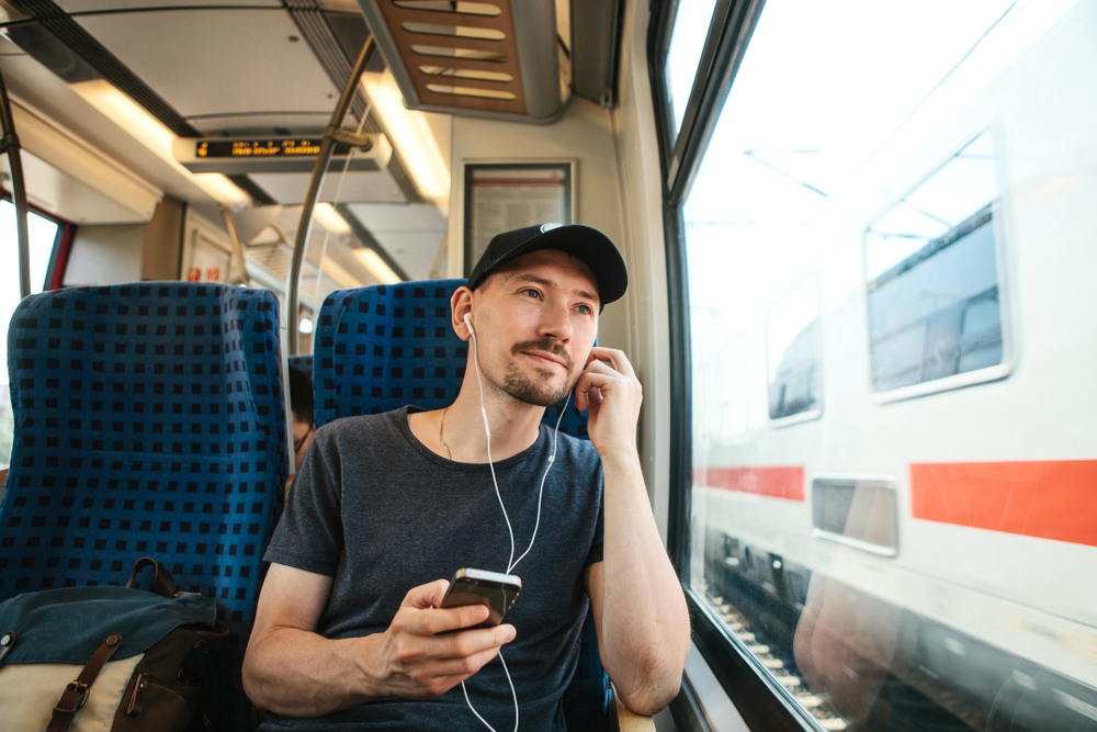 man-listening-to-podcast-on-train-traveling