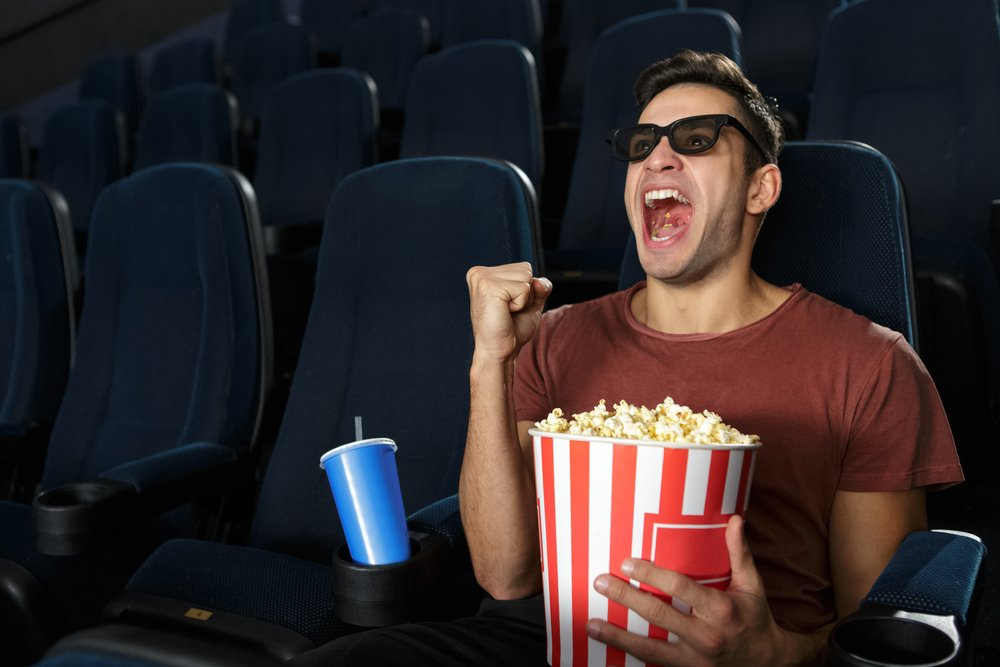 Young-man-watching-movie-at-movie-theater-wearing-3D-glasses