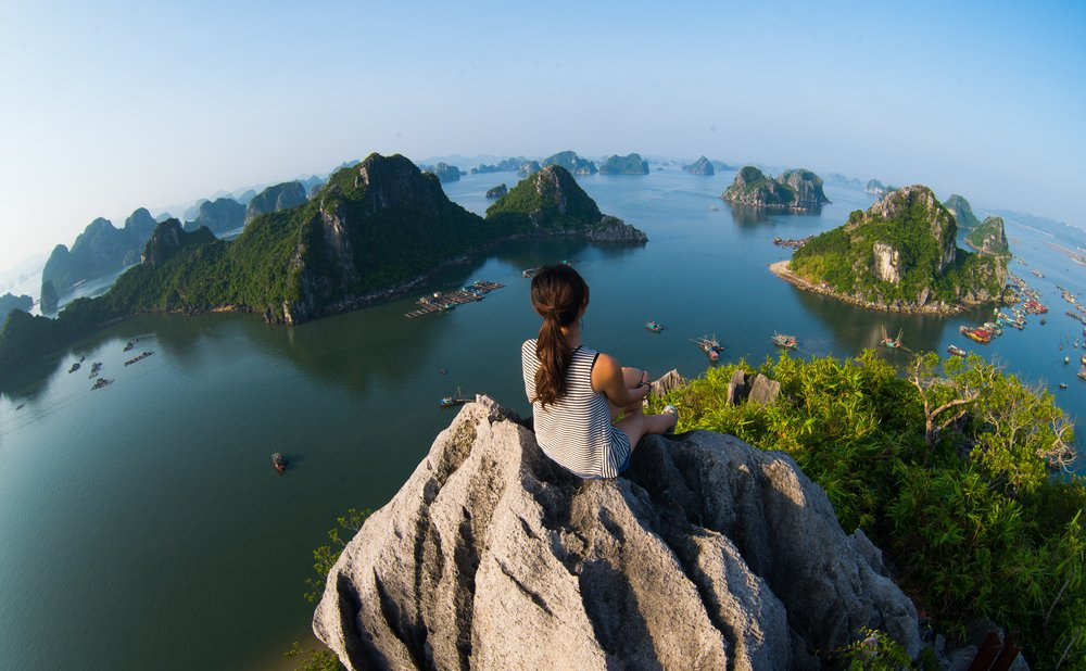 Woman sits on rock surrounded by foreign islands.