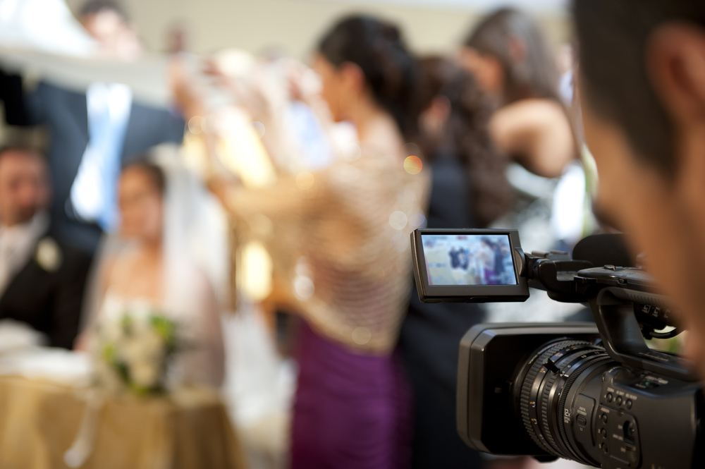 Man records wedding on video camera.